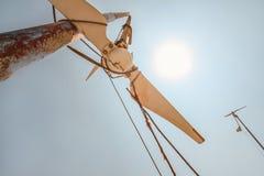 Olhando acima a turbina eólica quebrada pequena, sol forte do meio-dia que brilha na parte traseira fotos de stock
