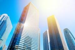 Olhando acima a vista no distrito financeiro, as silhuetas dos arranha-céus que a cidade reflete o céu azul, sol iluminam-se no T Fotografia de Stock Royalty Free