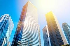 Olhando acima a vista no distrito financeiro, as silhuetas dos arranha-céus que a cidade reflete o céu azul, sol iluminam-se no T Imagem de Stock