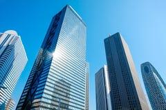 Olhando acima a vista no distrito financeiro, as silhuetas dos arranha-céus que a cidade reflete o céu azul, sol iluminam-se no T Fotos de Stock