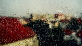Olhando a chuva através do vidro obscuro de uma janela filme