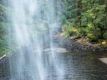 Olhando com cachoeiras na ponte de madeira do pé Imagem de Stock Royalty Free