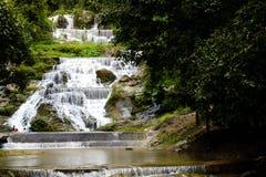 Olhando do lado distante para a água forte do fluxo das cachoeiras de Mae Phun no distrito de Laplae, Tailândia Imagens de Stock Royalty Free