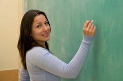 Olhando a escrita do estudante no quadro-negro Fotos de Stock
