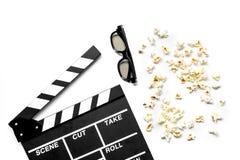 Olhando o filme Clapperboard, óculos de sol e pipoca do filme na opinião superior do fundo branco Fotografia de Stock