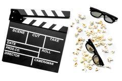 Olhando o filme Clapperboard, óculos de sol e pipoca do filme na opinião superior do fundo branco Imagens de Stock Royalty Free