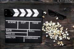 Olhando o filme Clapperboard, óculos de sol e pipoca do filme na opinião superior do fundo de madeira da tabela Foto de Stock