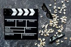 Olhando o filme Clapperboard, óculos de sol e pipoca do filme na opinião superior do fundo de pedra cinzento da tabela Fotografia de Stock Royalty Free