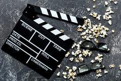Olhando o filme Clapperboard, óculos de sol e pipoca do filme na opinião superior do fundo de pedra cinzento da tabela Fotos de Stock Royalty Free