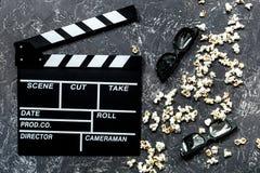 Olhando o filme Clapperboard, óculos de sol e pipoca do filme na opinião superior do fundo de pedra cinzento da tabela Imagens de Stock