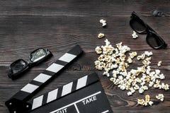 Olhando o filme Clapperboard, óculos de sol e pipoca do filme no copyspace de madeira da opinião superior do fundo da tabela Foto de Stock Royalty Free