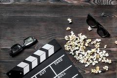 Olhando o filme Clapperboard, óculos de sol e pipoca do filme no copyspace de madeira da opinião superior do fundo da tabela Foto de Stock