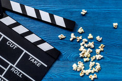 Olhando o filme Clapperboard e pipoca do filme na opinião superior do fundo de madeira azul da tabela Imagens de Stock