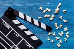 Olhando o filme Clapperboard e pipoca do filme na opinião superior do fundo de madeira azul da tabela Foto de Stock