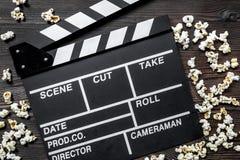 Olhando o filme Clapperboard e pipoca do filme na opinião superior do fundo de madeira da tabela Fotos de Stock Royalty Free