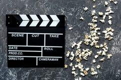 Olhando o filme Clapperboard e pipoca do filme na opinião superior do fundo de pedra cinzento da tabela Foto de Stock