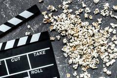 Olhando o filme Clapperboard e pipoca do filme na opinião superior do fundo de pedra cinzento da tabela Imagem de Stock