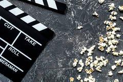 Olhando o filme Clapperboard e pipoca do filme na opinião superior do fundo de pedra cinzento da tabela Fotos de Stock Royalty Free