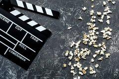 Olhando o filme Clapperboard e pipoca do filme na opinião superior do fundo de pedra cinzento da tabela Foto de Stock Royalty Free