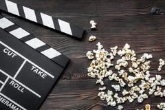 Olhando o filme Clapperboard e pipoca do filme no copyspace de madeira da opinião superior do fundo da tabela Fotos de Stock