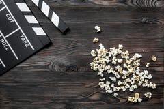 Olhando o filme Clapperboard e pipoca do filme no copyspace de madeira da opinião superior do fundo da tabela Imagens de Stock