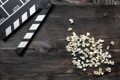 Olhando o filme Clapperboard e pipoca do filme no copyspace de madeira da opinião superior do fundo da tabela Imagens de Stock Royalty Free