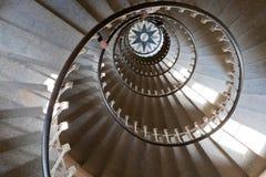Olhando para baixo em escadas circulares do farol, mãos dos turistas imagem de stock