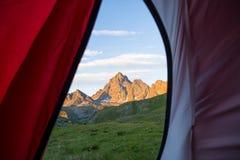 Olhando para fora a montanha ajardine no nascer do sol do interior da barraca de acampamento Aventure-se a viagem nos cumes europ Foto de Stock Royalty Free