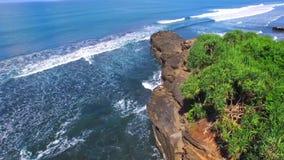 Olhando sobre, os penhascos e as ondas do mar que ligação à praia, na costa de Bali Conceito ambiental da sustentabilidade video estoque