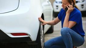Olhando um veículo danificado O louro da mulher inspeciona dano do carro após um acidente filme