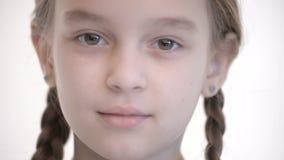 Olhar aberto do close-up da menina caucasiano com as tranças que abrem e que fecham os olhos Olhar neutro da emoção na câmera filme