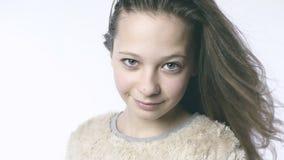 Olhar adulto de uma moça Menina bonita no movimento lento em um fundo branco vídeos de arquivo