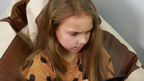 Olhar ansioso da mensagem da leitura do adolescente Perto acima de 9 anos de menina que usa o smartphone filme