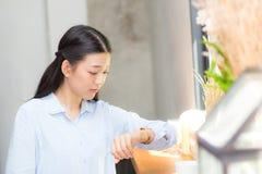 Olhar asiático bonito da jovem mulher no amigo de espera ou em alguém do relógio Foto de Stock