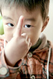 Olhar asiático do menino em seu dedo imagens de stock royalty free
