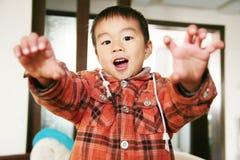 Olhar asiático do menino em seu dedo fotos de stock