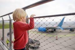 Olhar bonito do rapaz pequeno em aviões na plataforma de observação no aeroporto da cidade europeia pequena antes do voo Passagei fotografia de stock
