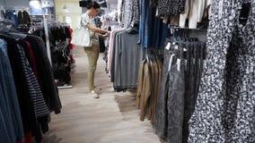 Olhar da compra da mulher sobre vestidos em ganchos vídeos de arquivo