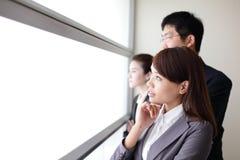 Olhar da equipe do negócio através da janela Imagem de Stock Royalty Free