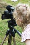 Olhar da menina ao inventor da câmara de vídeo Imagem de Stock