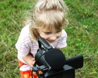 Olhar da menina ao inventor da câmara de vídeo Foto de Stock