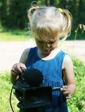 Olhar da menina ao inventor da câmara de vídeo Foto de Stock Royalty Free