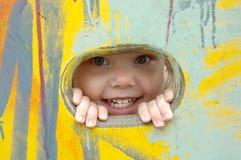 Olhar da menina fora do furo na parede pintada. Imagens de Stock Royalty Free