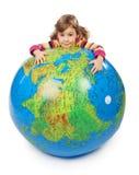 Olhar da menina fora do globo inflável e de abraçá-lo imagens de stock royalty free