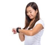 Olhar da mulher em seu relógio esperto para a taxa do batimento cardíaco imagens de stock royalty free