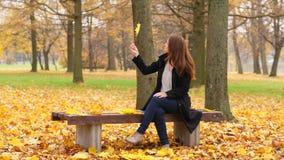 Olhar da mulher na folha caída amarela em sua mão vídeos de arquivo