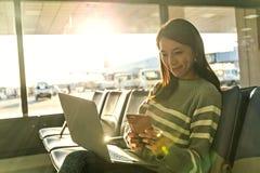 Olhar da mulher no telefone celular com seu portátil no aeroporto Imagens de Stock Royalty Free