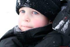 Olhar da perfuração do menino na neve Fotos de Stock Royalty Free