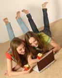 Olhar das meninas no portátil da tela Fotografia de Stock