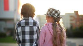 Olhar de duas crianças em se e no riso A menina tem um chapéu à moda video estoque